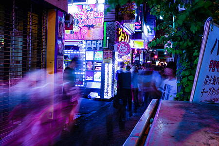 people in clothing on motion on pathway between buildings during nighttime
