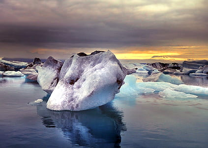 white ice berg on body of water during dawn