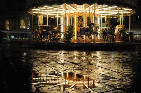 horse carousel with turned on lights during daytime