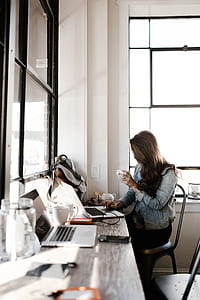 woman holding white ceramic cup while working on laptop