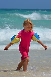 girl in pink wet suit near sea at daytime