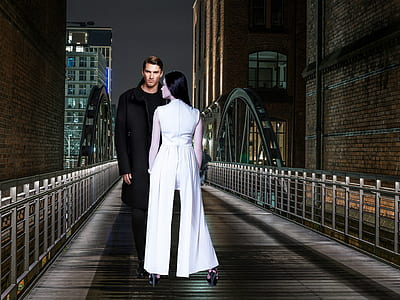 man standing on bridge with a woman in front of him