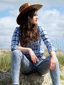 woman sitting on grass wearing brown hat under daytime