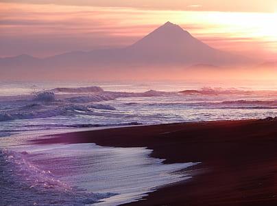 sea of water near mountain during sunrise
