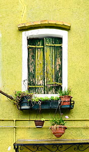 white and black wooden window on yellow concrete wall