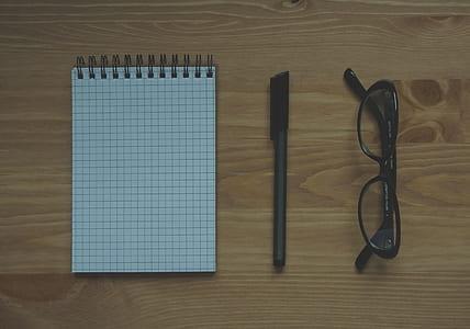eyeglasses, marker, and spring book