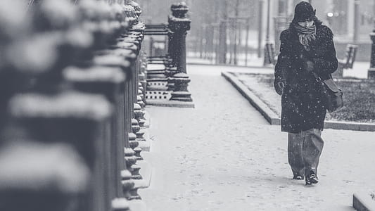 grayscale photography of a person in black trench coat walking across the street during winter weather