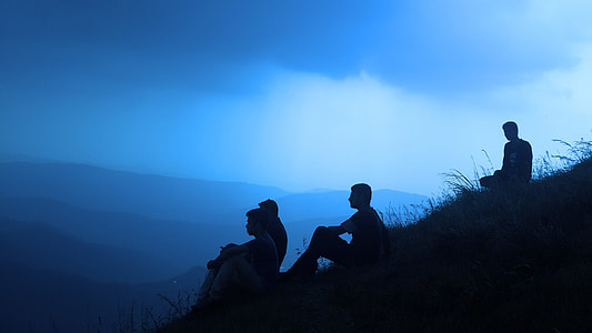 four men sitting on hill