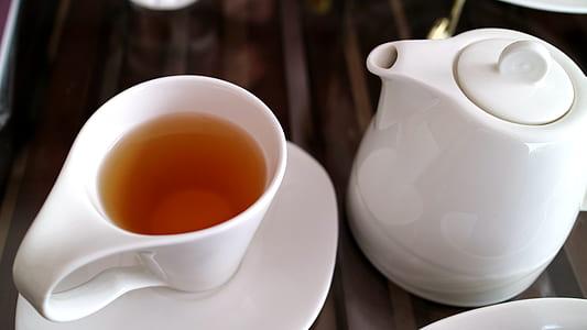 white ceramic mug on saucer beside teapot