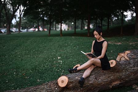 woman wearing black sleeveless dress sitting on brown tree log