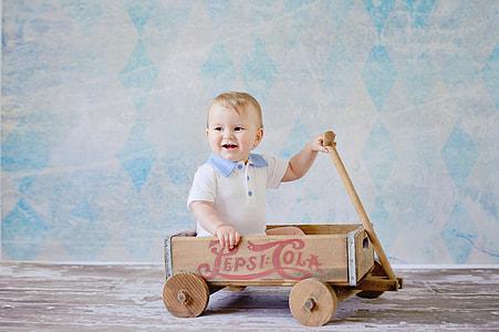 toddler sitting on brown Pepsi-Cola pull wagon