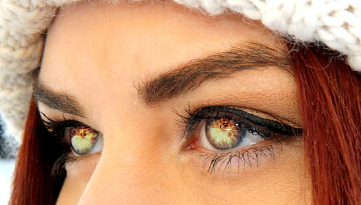 photo of woman's eyes reflecting fire