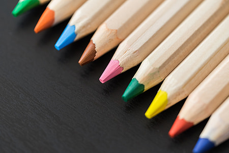 Colored Pencils in a Row on Black Desk Close Up