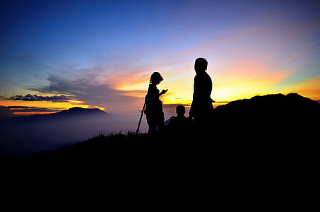 silhouette of three persons atop mountain
