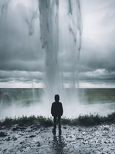 person standing facing on geyser photograph