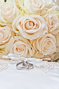 white flower bouquet and two silver-colored rings