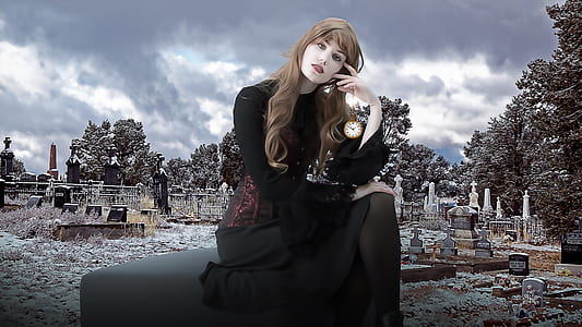 woman in black long-sleeved dress sitting while holding her head and looking straight to the camera