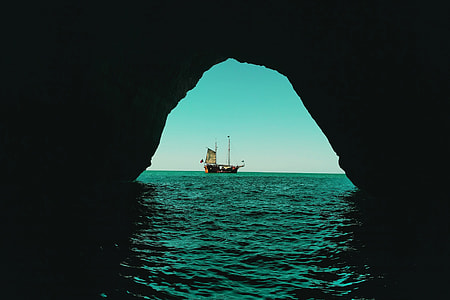 View of a boat from an ocean water cave
