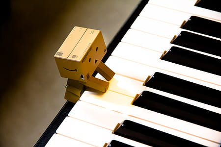 brown cardboard character on top of white piano