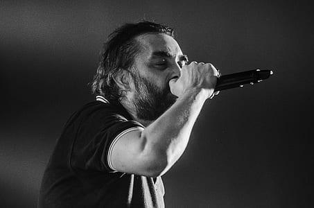 Man Singing Wearing Black Polo Shirt