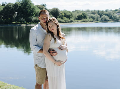 man beside pregnant woman near body of water
