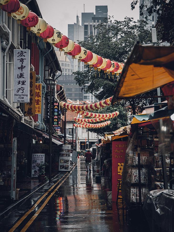 man walking on wet road of China during daytime