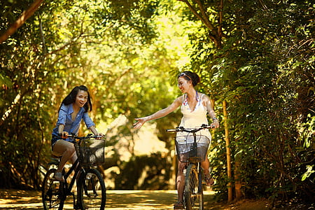 two woman riding on a city bicycles