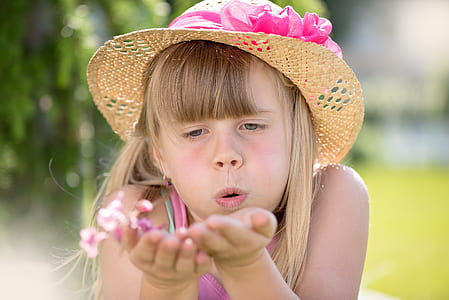 girl blowing pink petaled flowers