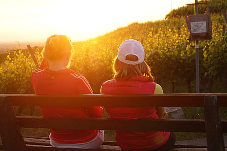two women sitting on wooden bench facing the sunlight