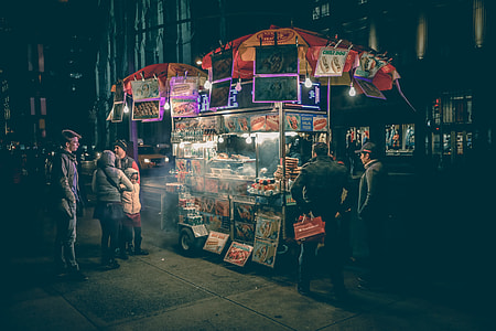 photography of people standing near food stand during night time