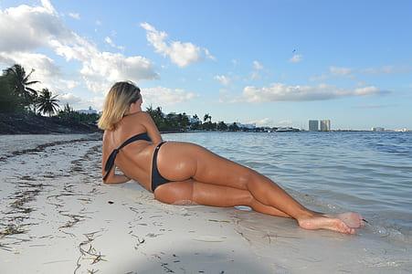 woman wearing black bikini sunbathing on beach