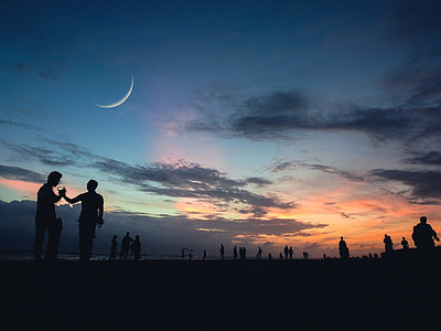 silhouette of people under crescent moon during golden hour
