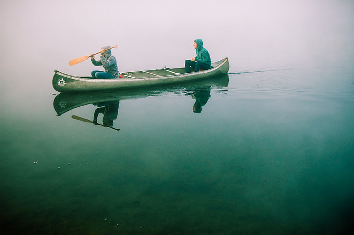 Two People Rowing On Green Wooden Paddle Boat
