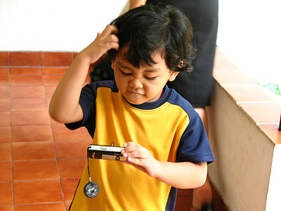boy holding point-and-shoot camera