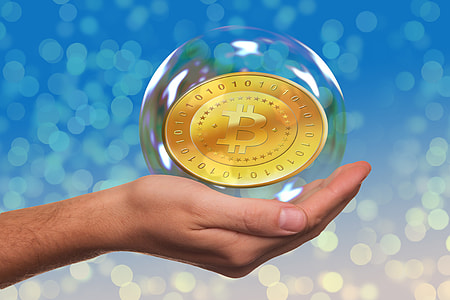person's left hand holding bubble with Bitcoin inside