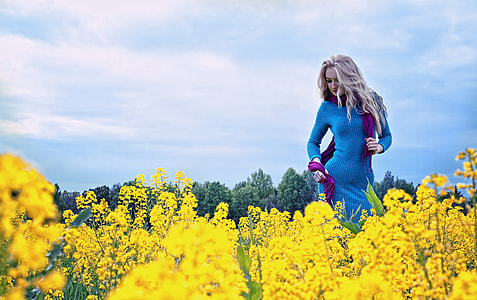 woman in blue long-sleeved dress stands on yellow petaled flower field