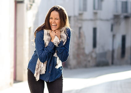 woman laughing near high rise building during daytime