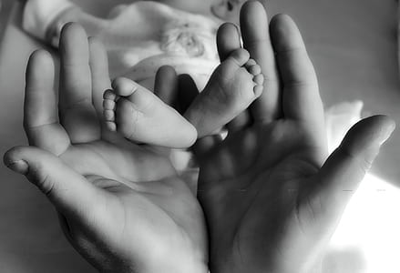 person holding baby feet