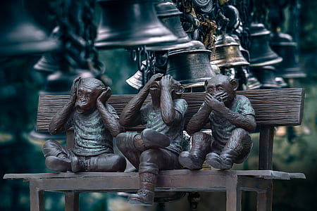 Three Wise Monkeys on brown wooden bench