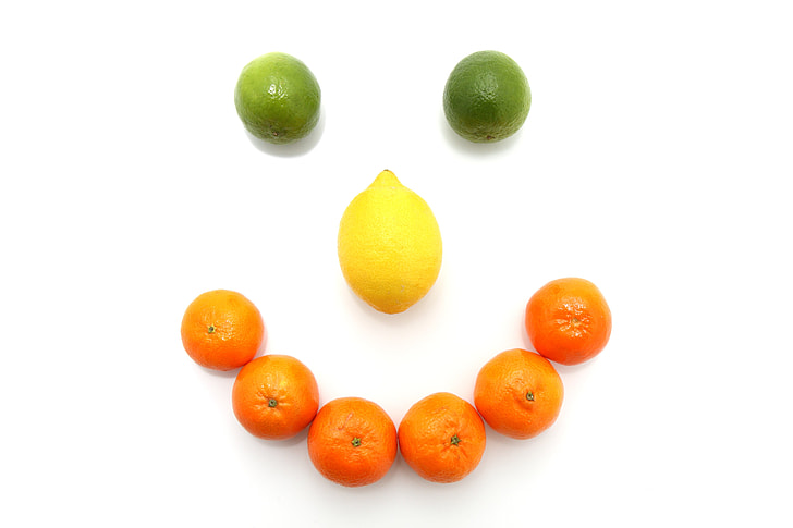 orange fruits and lemon formed smiley on white surface