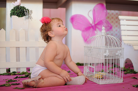 baby's white bottoms beside white metal birdcage on pink surface