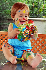 boy wearing blue shirt holding paint on table
