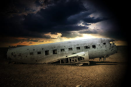 photo of wrecked airplane on brown sand