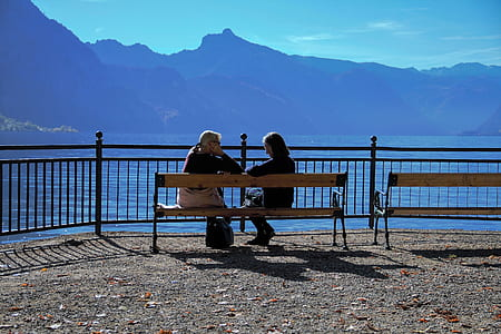 women seating on brown wooden bench