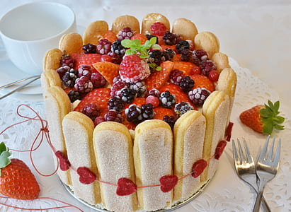 round strawberry cake beside two table forks