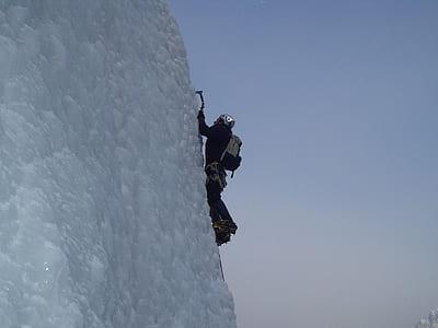 man climbing a snow covered mountain