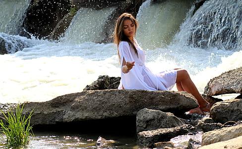 woman sitting on rock beside waterfalls