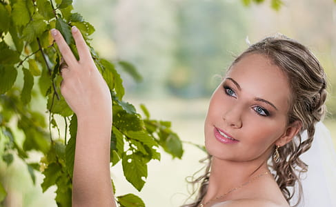 photo of woman holding leaves