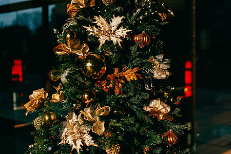 brown and gold-colored ornaments on green Christmas tree