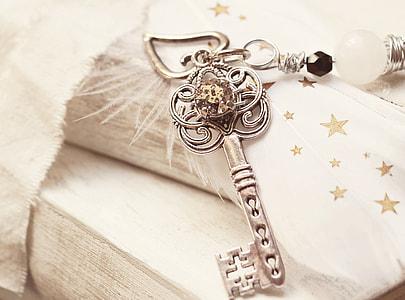 silver-colored skeleton key pendant on white textile